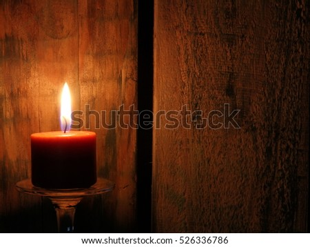 Brown Candle Burning Against Rustic Wood Background - photograph of a single brown candle burning warmly against a background of rustic wood. Blemishes natural to wood.  Space for text.