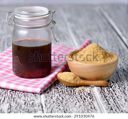 Brown cane sugar and honey on wooden board. - stock photo