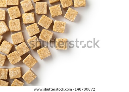 Brown cane sugar cubes on white background. Copy space. Top view - stock photo