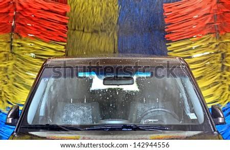 Brown car inside carwash - stock photo