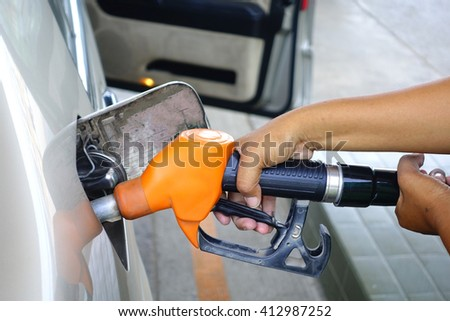 Brown car with Orange Fuel nozzle on a gas station