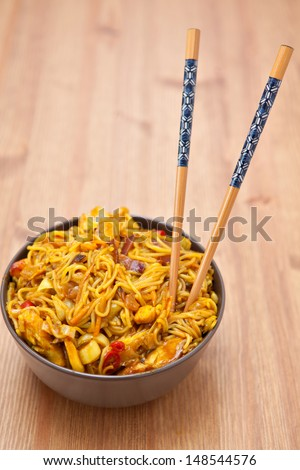 Brown ceramic bowl with a portion of Singapore noodles - stock photo