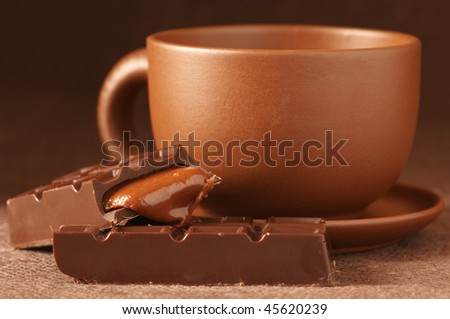 Brown ceramic cup of coffee and broken chocolate bar with caramel stuffing on brown canvas. - stock photo