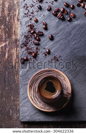 Brown ceramic cup of coffee and coffee beans over black slate as background. With copy space at right. Top view. - stock photo