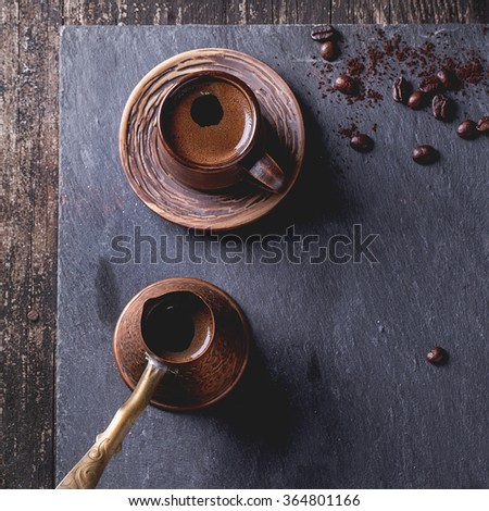Brown ceramic cup of coffee, old copper cezve and coffee beans. Over black slate as background. With copy space at centre. Top view. Square image - stock photo