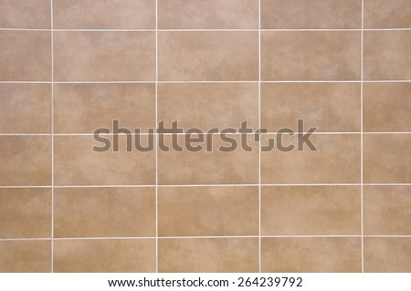 Brown ceramic tiles with white fugue on wall closeup