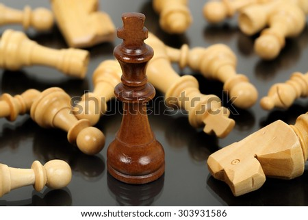brown chess king surrounded by fallen opponents - stock photo