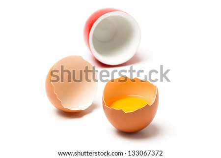 Brown chicken egg and red egg cup, isolated on white background - stock photo