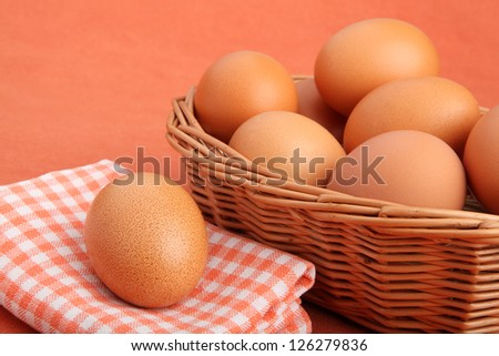 Brown chicken egg on vintage tablecloth and eggs in the basket