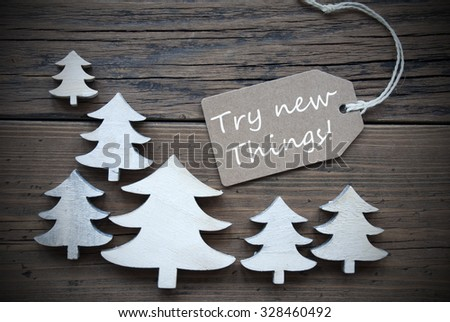 Brown Christmas Label With Ribbon On Wooden  Background With White Christmas Trees. Vintage Style. Label With English Quote Try New Things For Christmas Or Season Greetings - stock photo