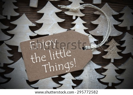 Brown Christmas Label With Ribbon On Wooden Christmas Trees Background. Vintage Style. Label With English Quote Enjoy The Little Things For Christmas Or Season Greetings.Close Up Or Macro - stock photo