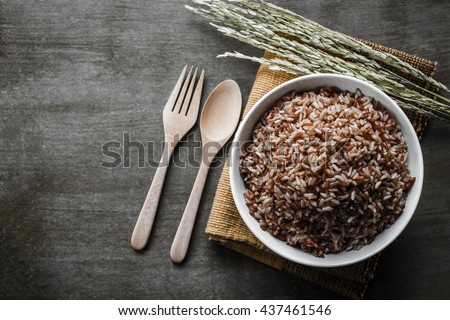 Brown/Coarse Rice with wooden spoon and fork, rice seed . Top view.