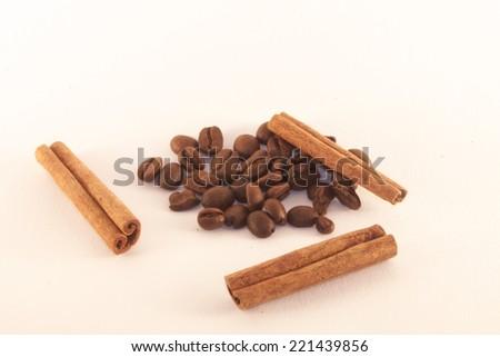 Brown coffe beans and light brown cinnamon sticks - stock photo