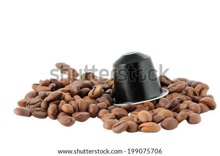 Brown coffee beans and capsules on a white background - stock photo