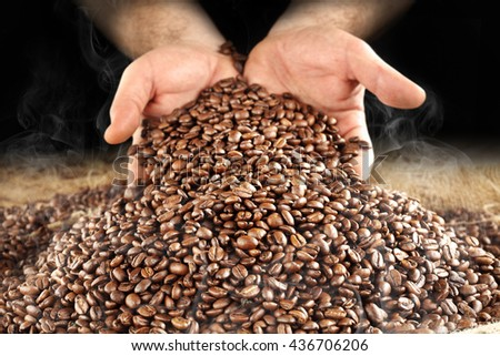 brown coffee beans and hands and smoke and sack  - stock photo