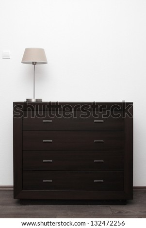 brown commode with lamp in bright minimalism interior - stock photo