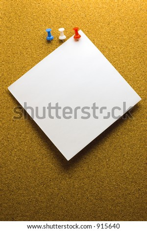 Brown cork board with pinned paper note and three pins - stock photo