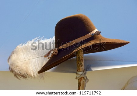 brown cowboy hat with a white feather attached