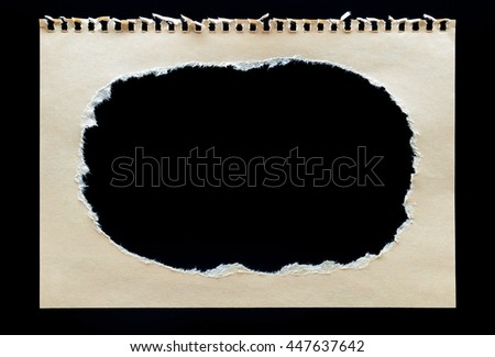 Brown craft paper with hole torn in paper with rough edges isolate on chalkboard background. Stick notes paper craft  texture and design - stock photo