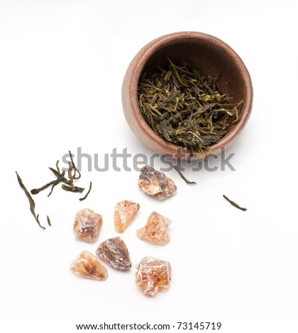 Brown crystal sugar and a tea cup with japanese green tea - stock photo