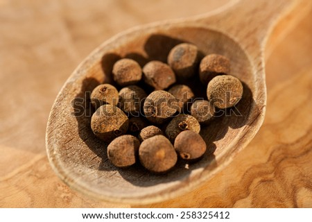 Brown dark whole allspice dry fruits portion on wooden spoon macro, Pimenta dioica raw spice unripe berries heap in day light, horizontal orientation, nobody.  - stock photo