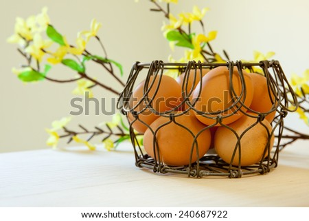 Brown eggs in a wire basket in natural light with yellow spring flowers in the background - stock photo