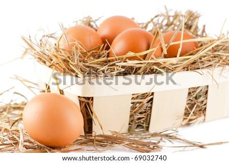 Brown eggs in wooden basket hay nest in chicken farm - stock photo