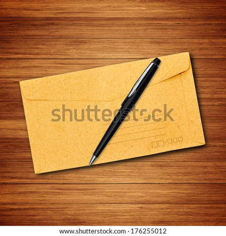 Brown envelope and pen on wood background - stock photo