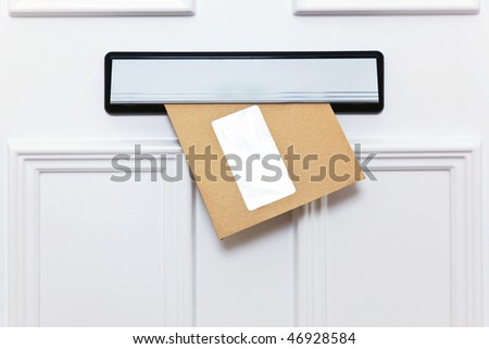Brown envelope in a front door letterbox blank window for you to add your own name and address details. - stock photo