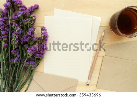 Brown envelopes and purple flowers with cup of tea on the wood desk, top view - stock photo