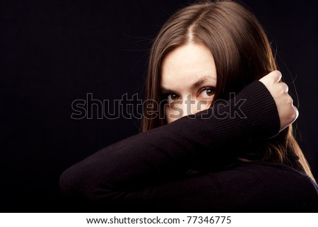 Brown eyed beauty is covering her face with hand.