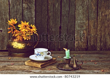 Brown eyed Susan flowers in an antique copper vase and an old book, teacup and saucer and antique candle holder on a rustic wood backdrop with copy space. - stock photo