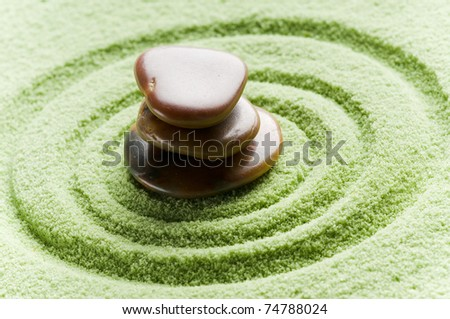 brown flat stones in blance in a circle on green sand - stock photo