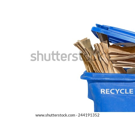 "Brown flattened corrugated boxes in blue plastic recycling bin. Open lid. White letters of the word ""RECYCLE"" on side of container. Isolated on a white background. Room for text. Copy space.  - stock photo"