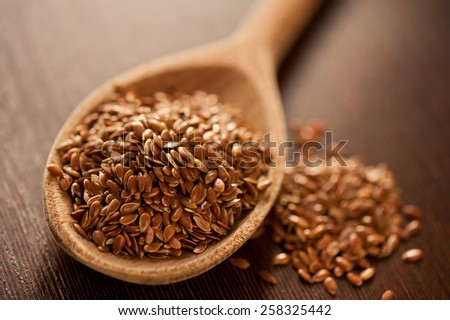 Brown flax seeds heap on wooden spoon closeup, healthy raw seeds portion in day light, horizontal orientation, nobody. - stock photo