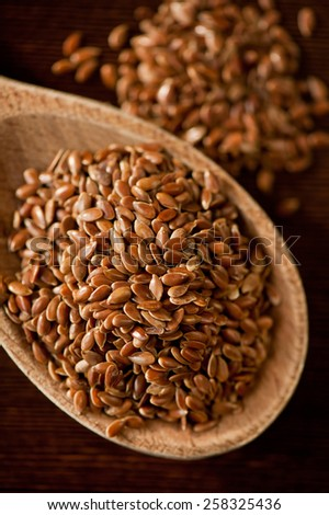 Brown flax seeds portion on wooden spoon closeup, healthy raw seeds heap in day light, vertical orientation, nobody.  - stock photo