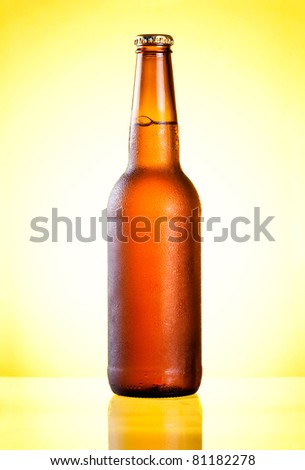 Brown full bottle fresh cold beer covered with condensate on yellow background - stock photo