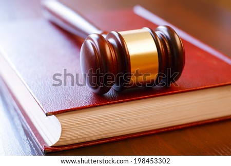 brown gavel and law book closed on wooden table in the courtroom