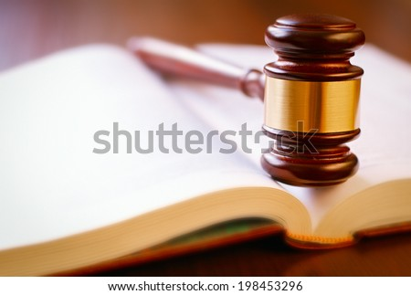 brown gavel and open book on a wooden table of the law in the courtroom - stock photo