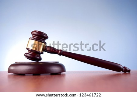 brown gavel with a brass band on a blue background - stock photo