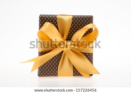 Brown gift box with dots with golden ribbon top view - stock photo