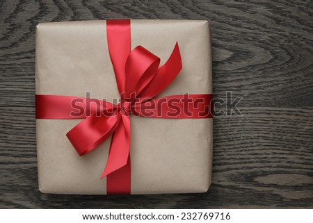 brown gift box with red bow on wood table, top view - stock photo