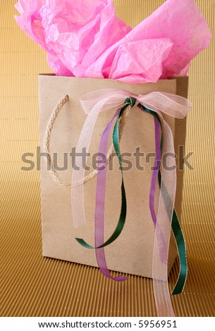 Brown gift box with ribbons and pink tissue paper