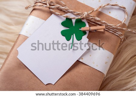 brown gift craft box with empty message cart with green shamrock clover leaf on wood background - stock photo