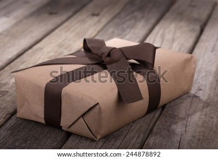 Brown gift package on old wood surface - stock photo