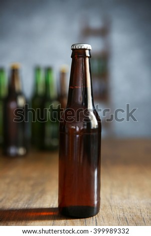 Brown glass bottle of beer on wooden table - stock photo