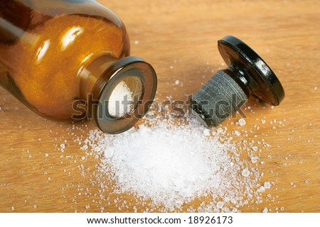 Brown glass bottle with spilled white powder - stock photo