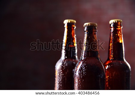 Brown glass bottles of beer on blurred background - stock photo