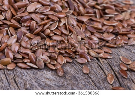Brown grains flax close-up. On the texture wooden background. - stock photo
