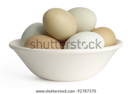 Brown, green and blue chickens eggs in a bowl isolated on white background with shadow - stock photo